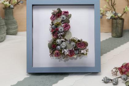 Monogramm mit Trockenblumen im Bilderrahmen