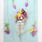 Hängegesteck mit Luffa Gurke und Frühlingsblumen in Reagenzgläsern