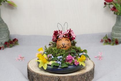 Osterdeko: Osterei mit Hasenohren und Blumenring